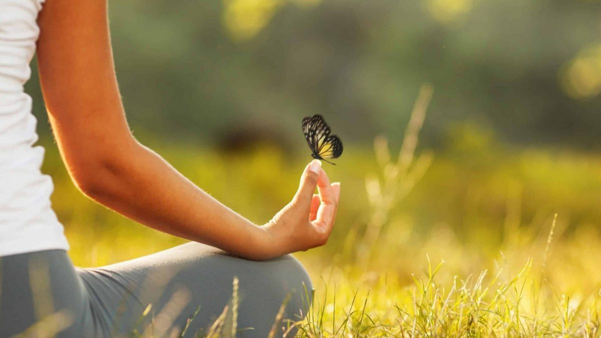 Mariposa sobre una mujer practicando meditación